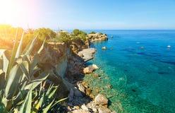 Waves break on rocky shore. Coast and beach resort village. Road along a rocky cliff. Tourist beach resort in village. Crete island, Greece Royalty Free Stock Image