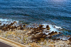 Waves break on rocky shore Rethymno, Crete, Greece. Waves break on rocky shore. Raging sea an elemental power in a storm. Clear day at sea coast. Tourist beach Stock Photos