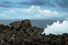 Waves break on rocky shore. Tourist beach resort in Nuca Dua of Bali Stock Photography