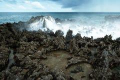 Waves break on rocky shore. Tourist beach resort in Nuca Dua of Bali Stock Photos
