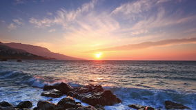 Waves break about stones at sunrise stock footage