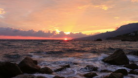 Waves break about stones at sunrise stock video footage