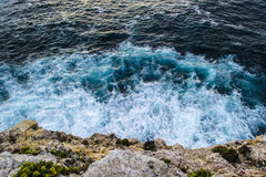 Waves breaking against the cliff face in Portugal Stock Images