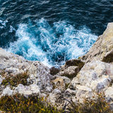 Waves breaking against the cliff face in Portugal. Frothy white waves breaking against the surface of the cliff face. Blue water with the sun reflecting off the stock photos