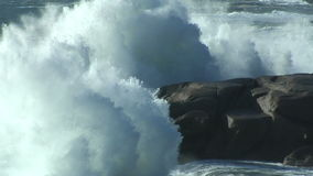 Waves breaking against rocks on ocean shoreline. Storm surge stock footage