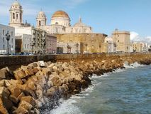 Cadiz Spain seafront. Waves breaking on the barrier near the city& x27;s cathedral Royalty Free Stock Photography