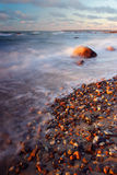 Waves breaking on beach. Scenic view of waves breaking on rocky sunlit beach with slow motion blur Stock Photo