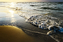 Waves breaking on the beach at sunset. Royalty Free Stock Images