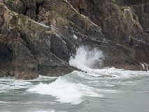 Waves Breaking on Cliff. Waves breaking against a rocky cliff Stock Photos