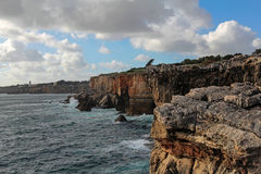 Waves breaking on the cliffs in Cascais, Portugal Stock Photos