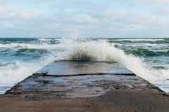Waves breaking on a concrete pier. In windy weather Stock Images