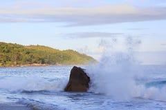 Waves breaking on granite boulders in beach of Stock Photos