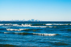 Waves breaking on lake with Toronto skyline in distance. Royalty Free Stock Photography