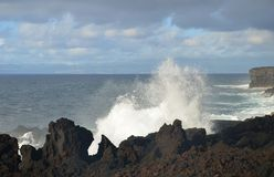Waves breaking on lava cliffs stock images