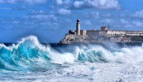 Malecon Sea Front, Havana. Waves Breaking on the Malecon Sea Front. El Morro Fort in Background, Havana, Cuba Stock Photos