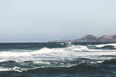 Waves Breaking Near Shore and Distant Lighthouse Royalty Free Stock Photos