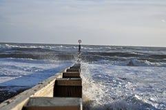 Waves breaking over groynes Royalty Free Stock Photo