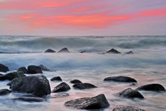 Waves breaking over rocks. With colorful sunset background, Baltic sea, Rugen island Royalty Free Stock Images