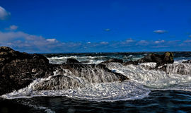 Waves breaking over rocks Stock Photos