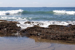Waves Breaking over Rocks Covered with Seaweed and Barnacles Stock Image