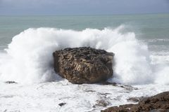 Waves breaking over rocks Stock Images