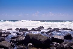 Waves breaking over rocks on a sunny day royalty free stock image