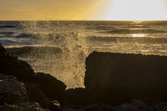 Waves breaking over rocks at sunset Royalty Free Stock Images