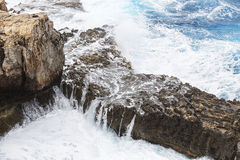 Waves breaking over a rocky ledge Royalty Free Stock Image