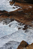 Waves breaking over the shoreline rocks Stock Images