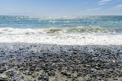 Waves Breaking on a Pebble Beach. Along the Coast of Vancouver Island on a Sunny Summer Day Stock Photo
