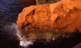 Waves breaking on a red rock Stock Photography