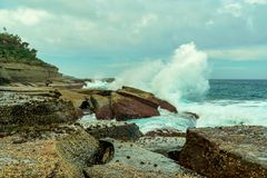 Waves breaking on Rock Formation, and rock pool on the Coastline at Pebbly Beach NSW Royalty Free Stock Images