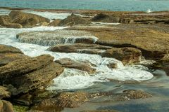 Waves breaking on Rock Formation, and rock pool on the Coastline at Pebbly Beach NSW Stock Photo