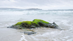 Waves breaking on a rock in a stormy day Stock Image