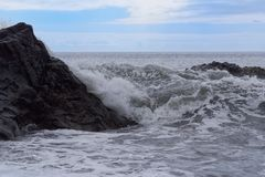 Waves breaking on the rock. Against blue cloudy sky at horizon. Portuguese island of Madeira royalty free stock images