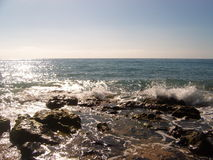 Waves breaking on the rocks. Sun sparkling on summer seas as waves break on the rocks stock photography