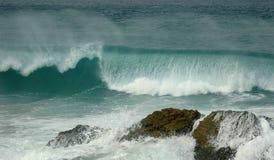 Waves breaking on rocks. Scenic view of waves breaking over rocks Stock Image