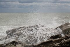 Waves breaking on rocks stock images