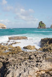 Waves breaking on rocks at tropical beach Stock Photos