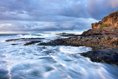 Waves breaking on rocky coast Stock Photos