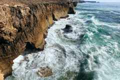 Waves breaking on rocky coast. Royalty Free Stock Images
