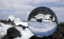 Waves Breaking on Rough Lava Rock in Glass or Crystal Ball stock photos