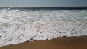 Waves breaking on sand. In a beach stock video footage