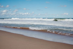Waves breaking on the sandy beach. Royalty Free Stock Image