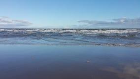 Waves breaking on sandy beach Stock Photo