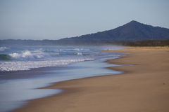 Waves breaking on sandy beach. Scenic view of waves breaking on sandy beach with mountain in background Stock Photo