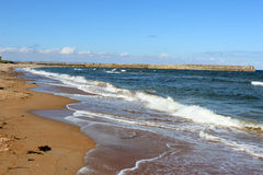 Waves breaking on sandy beach, St Andrews, Fife. View along a sandy beach at St Andrews, Fife, Scotland with waves breaking on the beach at high tide and the stock image