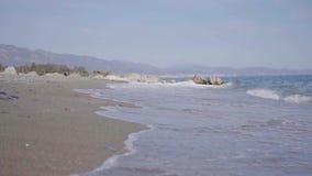 Waves breaking on a sandy beach stock video footage