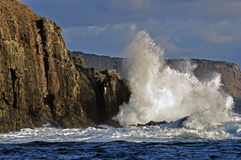 Waves breaking on sea cliffs stock photo