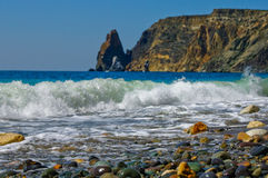 Waves breaking on seashore. Scenic view of waves breaking on pebbled beach with cliffs in background Stock Images